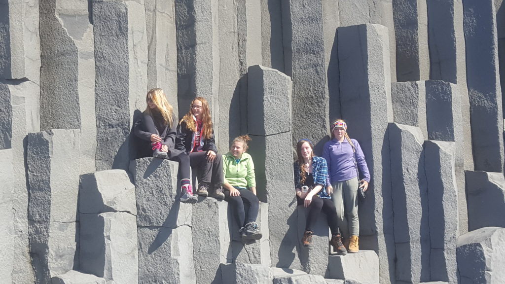 Travel Troop climbs on the basalt columns